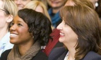 Two women in a crowd smiling.