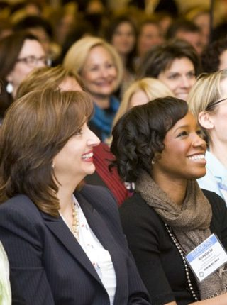 women at an event smiling